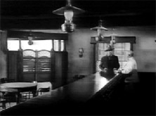 My Darling Clementine (1946). Ford's composition converges on Wyatt: the lines formed by the three lamps and bar ram into his guts. Doom is his destiny. His enemies line up along the bar like feathers on an arrow aimed at Wyatt.
