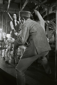 John B. Murray directing a nude model on a merry-go-round rocking horse in a scene at Luna Park, Melbourne