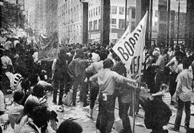 Chicago June 1970, Federal Plaza: a demonstration in support of Panther leader Bobby Seale; Nick reloads his Bolex (middleground, right of white banner)