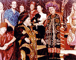 A still taken during the shooting of a sequence from The Magic Show at the Variety Arts Theatre in Los Angeles, 1982. From left to right: Allen Bracken (seated), Dave Egan (third from left), Don Bice, Orson Welles (seated), Bruce Gold, Oja Kodar and Kiki, Abb Dickson, and a female magic assistant.