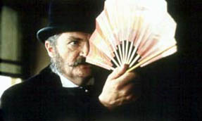 Gilbert warily regards a Japanese fan, as the inspiration for The Mikado dawns on him.