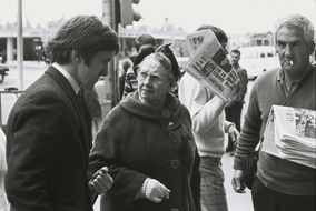 Graeme Blundell (market researcher) shocking another customer by purchasing 'girlie mags' at the newsstand outside Young & Jacksons Hotel, Swanston St, Melbourne, in The Naked Bunyip