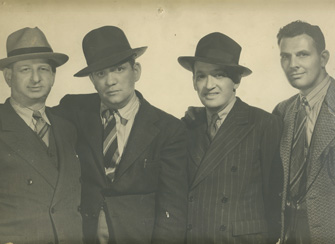 Sam Newfield, the most prolific director in the history of the American sound cinema, poses with his colleagues at a Producers Releasing Corporation dinner in the early 1940s. Left to right: Bert Sternbach, production manager; Sam Newfield, director; Sigmund Neufeld, producer; Jack Greenhalgh, cinematographer